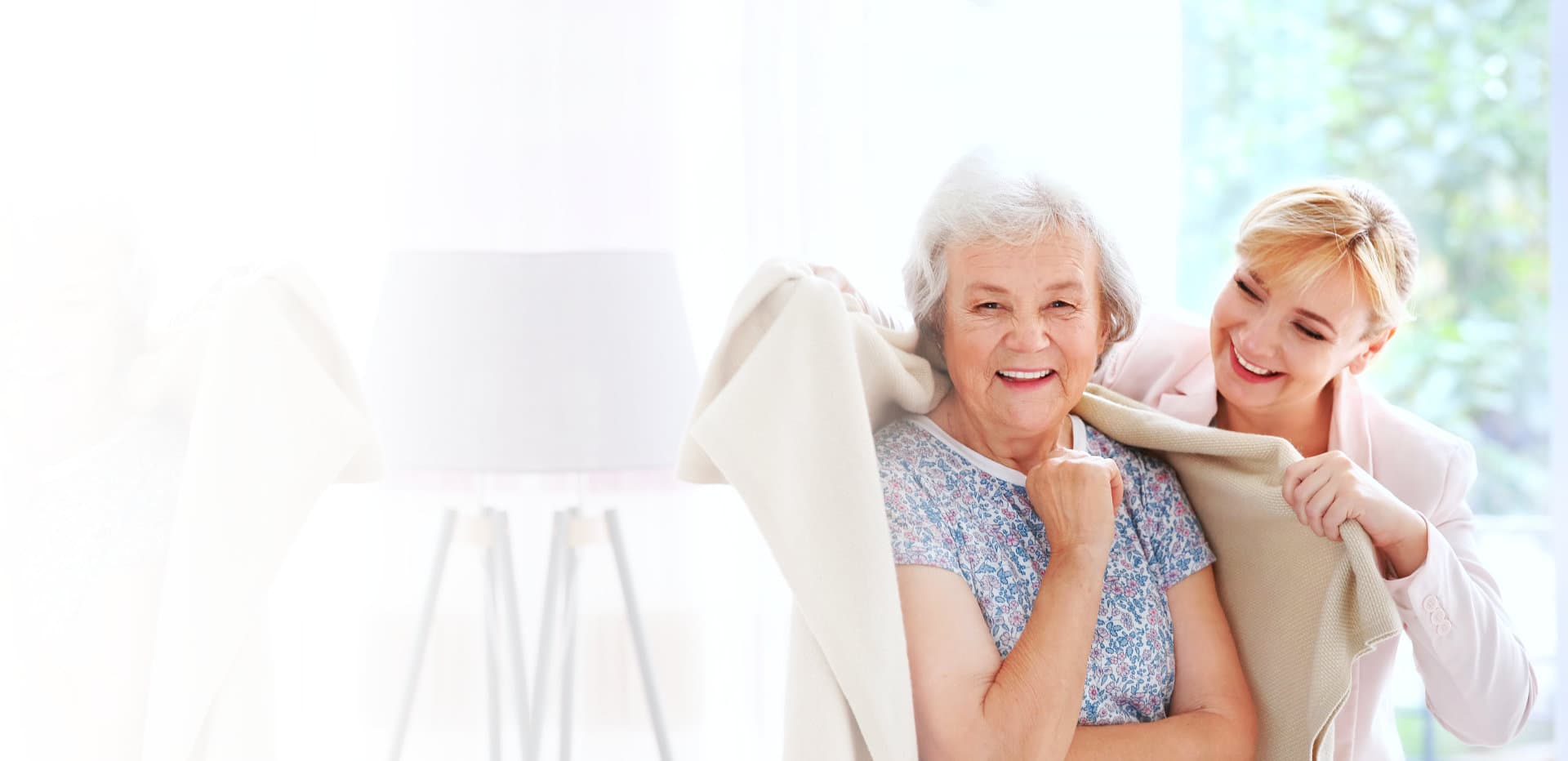 caregiver giving a blanket to senior woman smiling