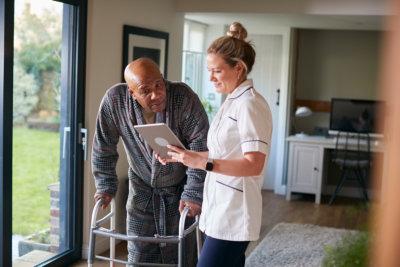 Senior Man In Dressing Gown Using Walking Frame Being Helped By Female Nurse With Digital Tablet