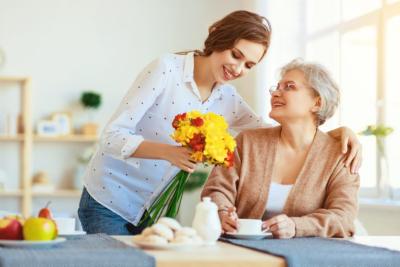Cheerful senior woman with her tender caretaker