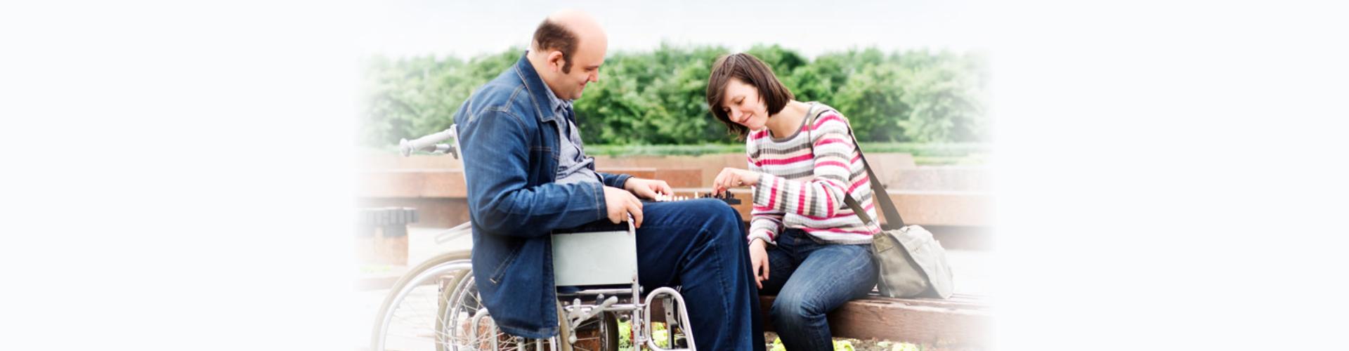 senior man in wheelchair with caregiver