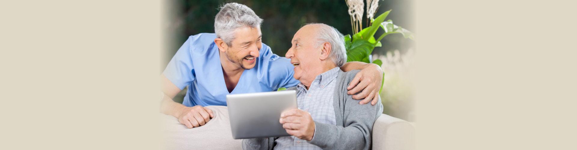 Laughing male caretaker and senior man using tablet computer at nursing home porch